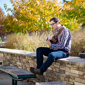 Male student playing guitar outdoors
