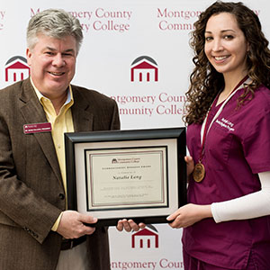 Dr. Pollock presenting plaque to Montco Student