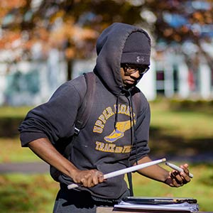 Student drumming on a notebook outside in the fall